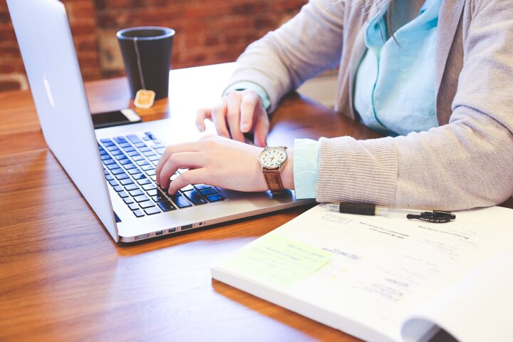 jeune femme devant un ordinateur et un bloc note